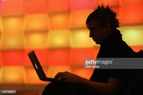 A participant sits with a laptop computer as he attends the annual Chaos Communication Congress of the Chaos Computer Club at the Berlin Congress...