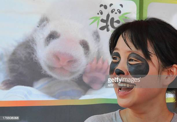 A participant smiles after having her face painted with a panda pattern as Taipei City Zoo held a 'babyshower' party to celebrate the onemonth...
