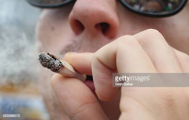 A participant smokes a marijuana joint while marching in the annual Hemp Parade on August 9 2014 in Berlin Germany Supporters of cannabis...