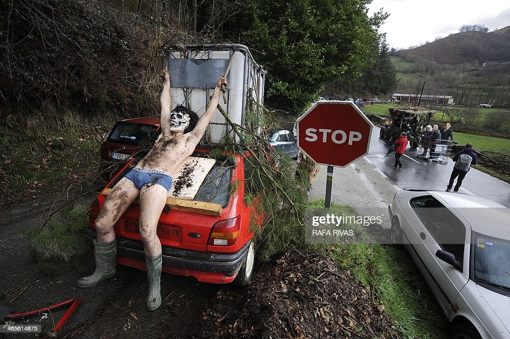 A participant sporting a mask rides tethered to a car during the ancient carnival of Zubieta, in the northern Spanish province of Navarra province, on January 28, 2014. The yearly three day festivities, revolving mainly around agriculture and principally sheep hearding, run on the last Sunday, Monday and Tuesday of January where Navarra Valley locals from three villages dress up and participate in a variety of activites as they perform a pilgrimage through each village.