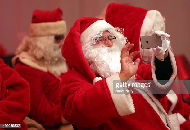 A participant takes a picture with his mobile phone during a gathering of volunteer student Santas and angels on November 28 2015 in Berlin Germany...