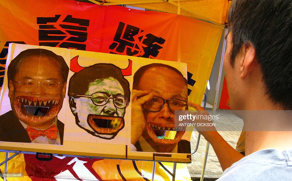 S SURNAME A participant throws balls in the mouths of pictures of (L-R) Hong Kong Chief Executive Donald Tsang, catering sector legislator Tommy Cheung Yu-yan and leading businessman Li Ka-shing, during a minimum wage demonstration in Hong Kong on June 13, 2010. The rally, organised by the Hong Kong Confederation of Trade Unions and the People's Alliance for Minimum Wage, was to promote the introduction of a universal minimum wage in Hong Kong of 33 HKD (4.25 USD) per hour. Cheung has become a hate figure among low paid workers and other unionists for suggesting last month that the minimum wage, to be implimented in 2011, should be set at an hourly rate of just 20 HKD. AFP PHOTO / Antony DICKSON