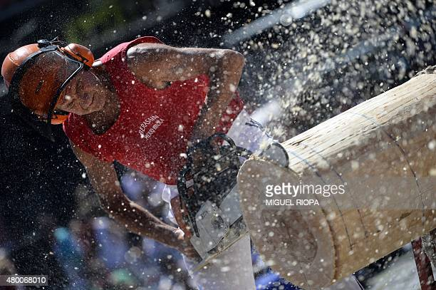 A participant uses a chainsaw to chop a trunk during the rural Basque sports championship of the San Fermin Festival in the Northern Spanish city of...