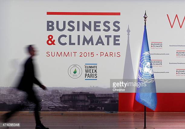 A participant walks in front of a poster during the 'Business and Climate Summit 2015' at the UNESCO headquarters on May 20 2015 in Paris France 200...