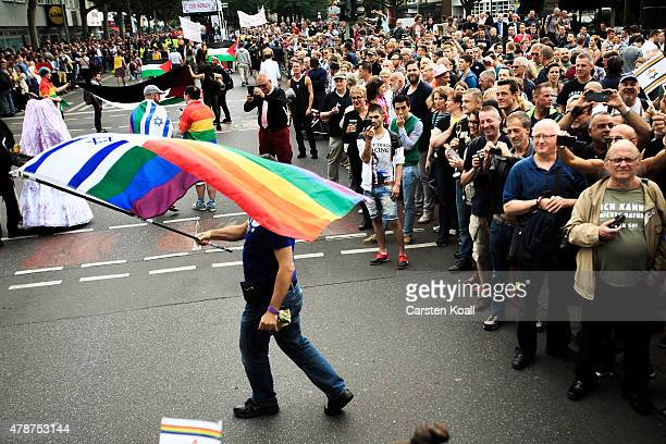 A participant waves a flag with the symbol of a israelian national flag and the rainow colors as he attends a Christopher Street Day parade on June...