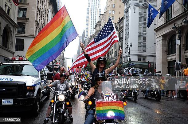 A participant waves a US and a rainbow flag from the back of the motorbike during the 2015 New York City Pride parade in New York on June 28 2015...