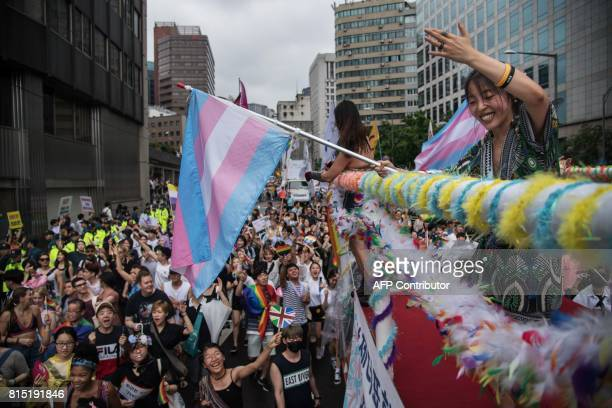 A participant waves from a float during a gay rights march in Seoul on July 15 2017 Thousands of people celebrated gay rights with song dance and a...