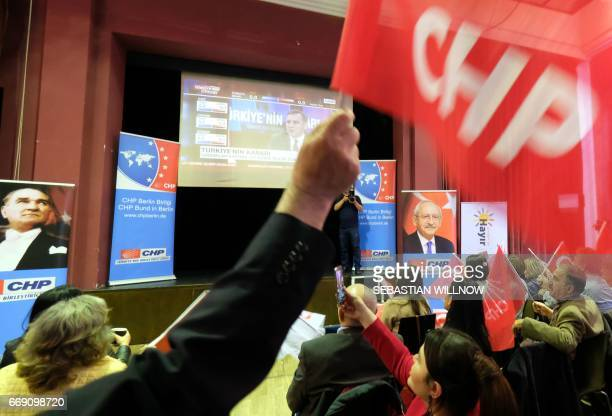 A participant waves the Turkish flag during an election party of the Republican People's Party in Berlin on April 16 2017 Turkey voted Sunday to...