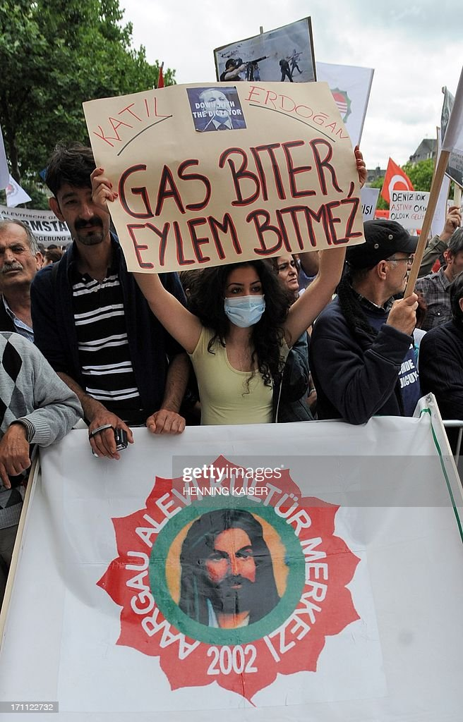 A participant wearing a gas mask hold a sign with a picture of Recep Erdogan that reads 'Killer' as she takes part in a protest against the Turkish government on June 22, 2013 in Cologne, western Germany. Tens of thousands of members of the Alevi community demanded the resignation of Turkish Prime Minister Recep Tayyip Erdogan and new elections. AFP PHOTO / HENNING KAISER GERMANY OUT