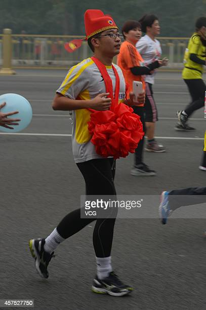 A participant wearing a red flower takes part in the 2014 Beijing International Marathon in the captical of China on October 19 2014 2014 Beijing...