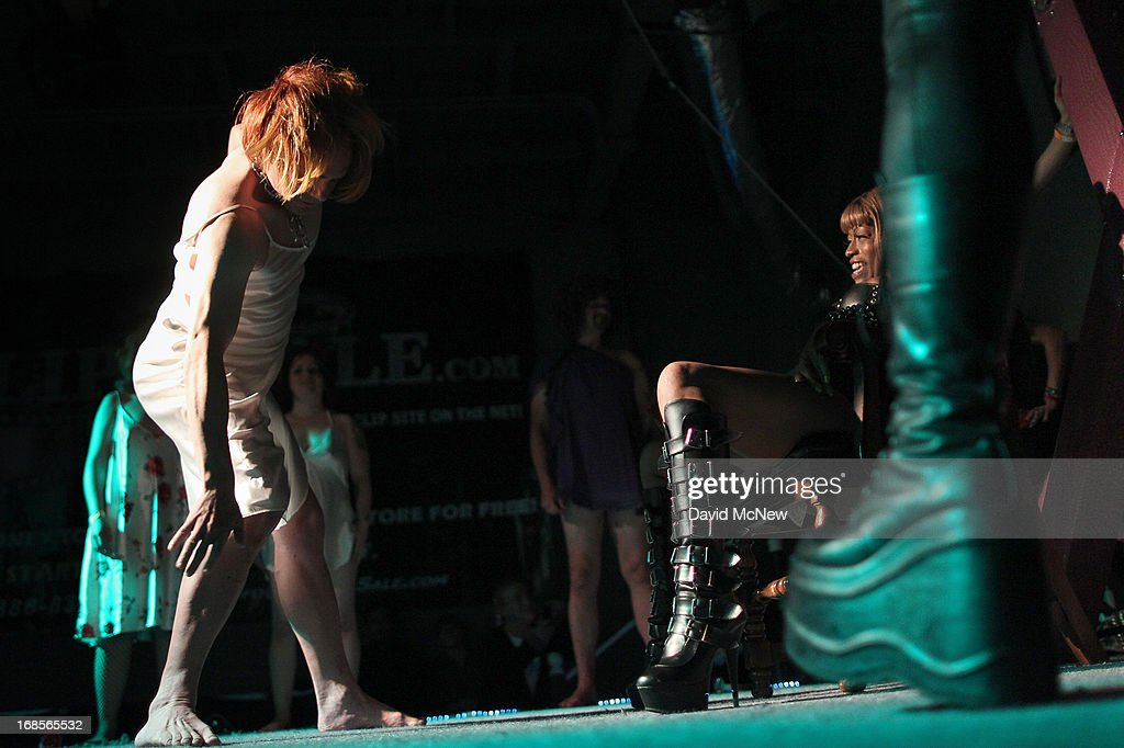 A participant wearing a wig and nightgown dances for a dominatrix as men and women compete in a contest to be the best submissive at a dungeon party during the domination convention, DomConLA, in the early morning hours of May 11, 2013 in Los Angeles, California. The annual convention was started in 2003 by fetish professional Mistress Cyan to bring together enthusiasts of BDSM (Bondage, Discipline, Dominance/Submission, and Sadomasochism) and other fetishes.