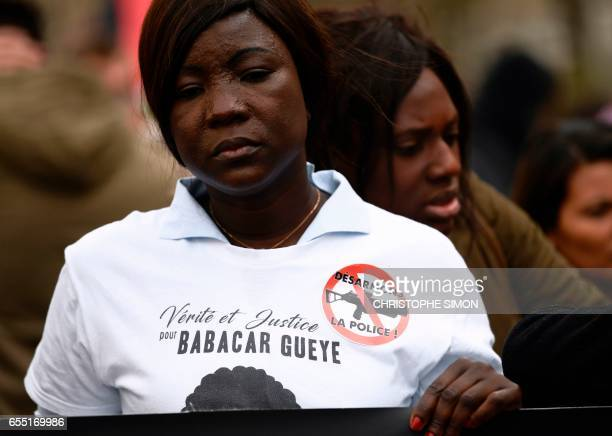 A participant wears a shirt reading 'Truth and justice for Babacar Gueye' as she takes part in a demonstration called by the families of the victims...
