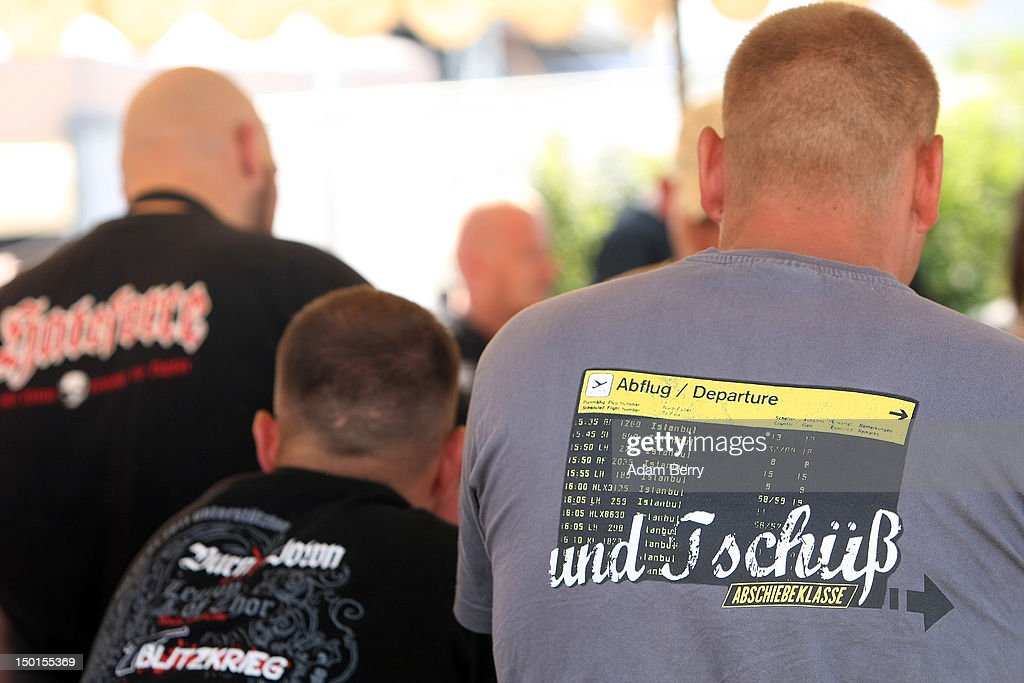 A participant wears a t-shirt with an illustration of a flight information board listing only flights to Istanbul behind the words 'And Goodbye' as he buys a beer at the German far-right Nationaldemokratische Partei Deutschlands - Die Volksunion (National Democratic Party, NPD) 'Pressefest' summer festival, organized by the party's publication, the 'Deutsche Stimme' (the German Voice), on August 11, 2012 in Pasewalk, Germany. The event took place in the German state of Mecklenburg-Vorpommern, known as a stronghold for the NPD, where the party won over 30% of the votes in two districts in state elections in 2011. There have been two attempts to legally ban the right-wing group, in 2003 and 2011, after a neo-Nazi terrorist cell murdered at least nine people of predominently Turkish background as well as one policewoman between 2000 and 2007.