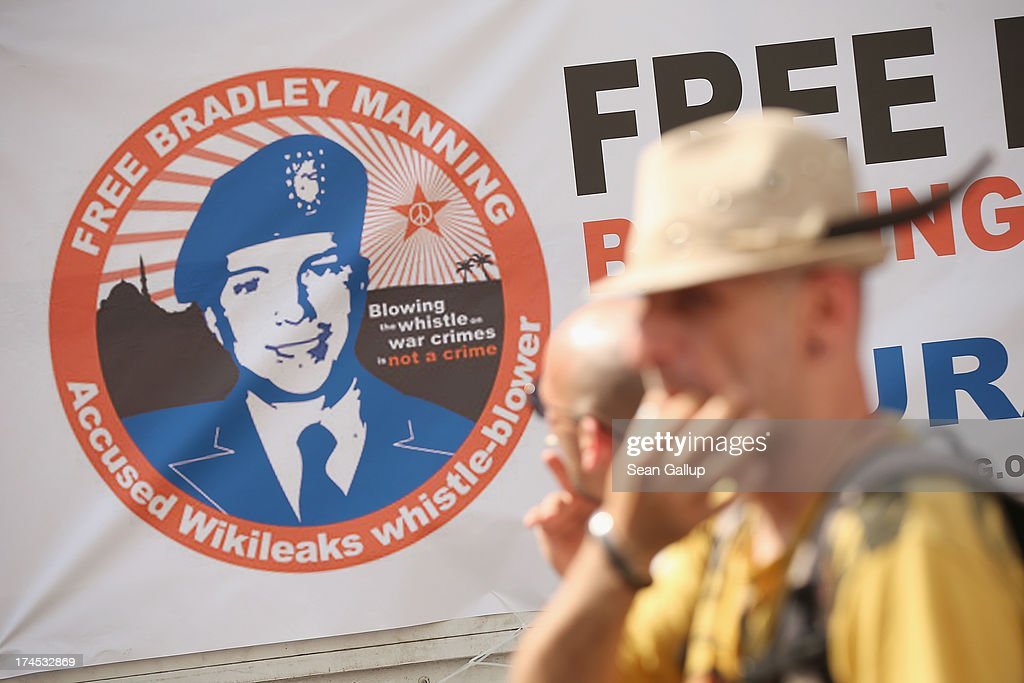 A participant whistles through his fingers as a sign behind shows support for US soldier and whistleblower Bradley Manning at a protest march against...