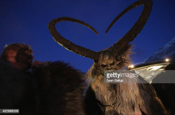 A participant who arrived by bus tries on his Krampus creature mask as other participants put on their costumes prior to Krampus night on November 30...