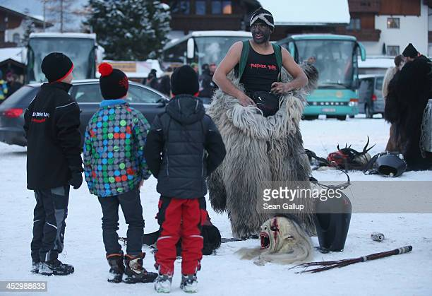 A participant who had arrived by bus chats with children while dressing as the Krampus creature prior to Krampus night on November 30 2013 in...