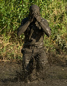 A participant wipes mud from his face after jumping in a pond.