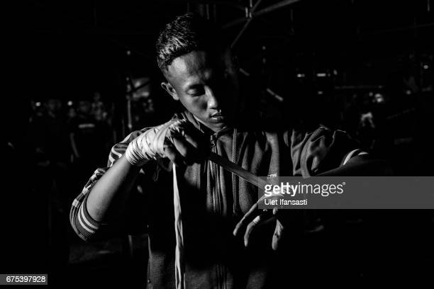 A participant wraps his hand as prepare to fight during the Pencak Dor competition at the yard of Lirboyo islamic boarding school on April 29 2017 in...