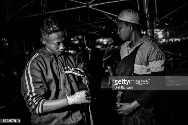 A participant wraps his hand as prepares before a fight during Pencak Dor competition at the yard of Lirboyo islamic boarding school on April 29 2017...