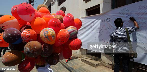 A participant writes a condolence message during the releasing balloons in memory of the victims of the massive earthquake last April 2015 marking...