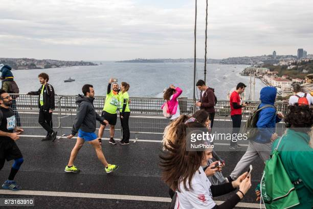 Participants and athlete run on the Bosphorus Bridge that links Istanbul's European and Asian side during the 39th annual Euroasia Marathon and...