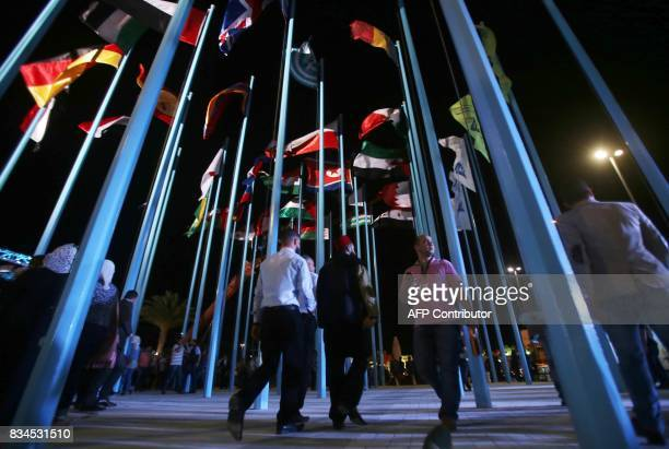 Participants and visitors walk past flags of various countries during the opening of the Damascus International Fair late on August 17 in the Syrian...