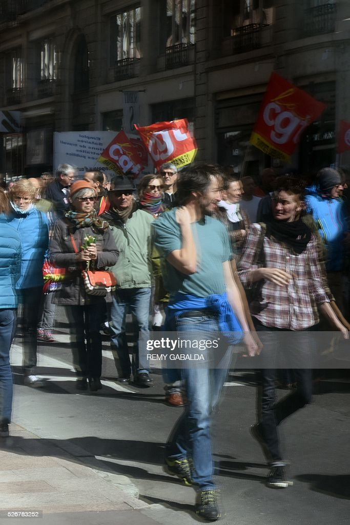 Participants are reflected in a shop window as they protest against the government's proposed labour law reforms during the traditional May Day demonstration in Toulouse, southern France, on May 1, 2016. / AFP / REMY