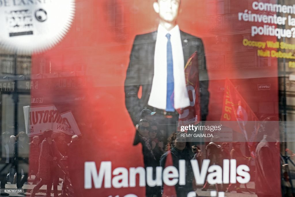 Participants are reflected in a shop window with a placard showing French Prime Minister Manuel Valls as they protest against the government's proposed labour law reforms during the traditional May Day demonstration in Toulouse, southern France, on May 1, 2016. / AFP / REMY