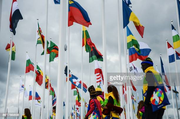Participants are walking in front of the flags of the countries worldwide during the Grand Opening Ceremony of 19th World Festival of Youth and...