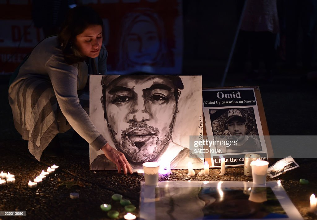 Participants arrange candles next to the portriat of an Iranian refugee, who died after setting himself on fire, in Sydney on April 30, 2016. The 23-year-old known as Omid set fire to himself on April 27, 2016 on the remote Pacific island where he had been sent by Australia, which refuses to resettle boat people even if found to be genuine refugees. / AFP / SAEED