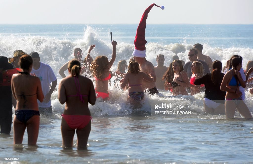 Participants at the annual Pier Plaza Plunge spend their few minutes in the chilly waters of the Pacific Ocean off Huntington Beach, California, for the New Year's Day tradition on January 1, 2014. AFP PHOTO/Frederic J. BROWN
