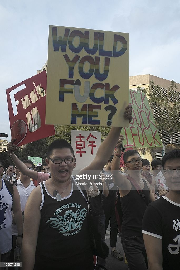 Participants at the annual Taipei Gay and Lesbian Pride Parade holding placards while parading through the city streets. The festival like parade attracts people from all over Taiwan and worldwide.