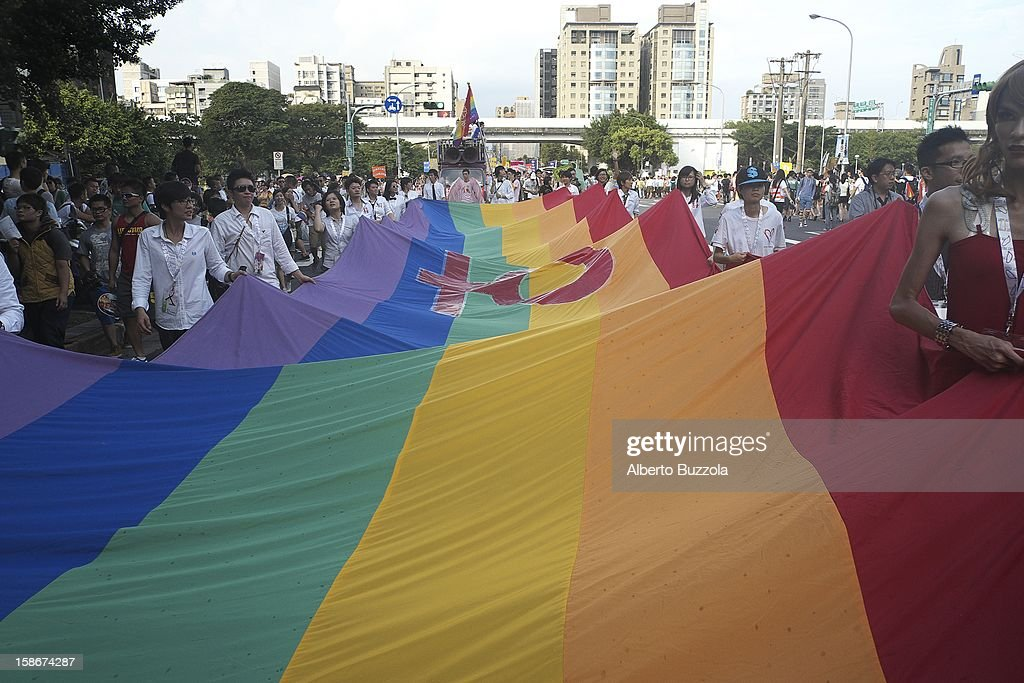 Participants at the Taipei Gay and Lesbian Pride Parade holding a giant rainbow flag..