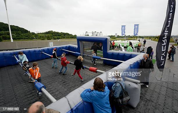 Participants attemp at a oversized table soccer game at the flyeralarm stand prior to the Women's International Friendly match between Germany and...