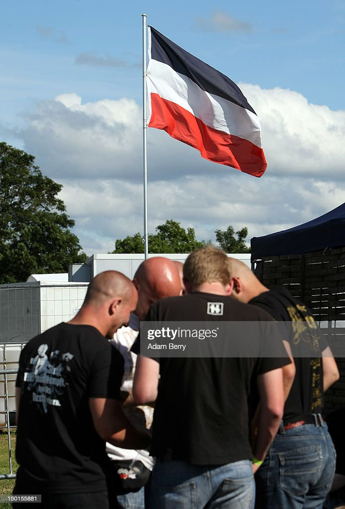 Participants attend the German far-right Nationaldemokratische Partei Deutschlands - Die Volksunion (National Democratic Party, NPD) 'Pressefest' summer festival, organized by the party's publication, the 'Deutsche Stimme' (the German Voice), in front of a former German national flag on August 11, 2012 in Pasewalk, Germany. The event took place in the German state of Mecklenburg-Vorpommern, known as a stronghold for the NPD, where the party won over 30% of the votes in two districts in state elections in 2011. There have been two attempts to legally ban the right-wing group, in 2003 and 2011, after a neo-Nazi terrorist cell murdered at least nine people of predominently Turkish background as well as one policewoman between 2000 and 2007.