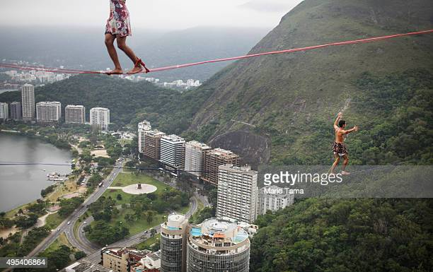 Participants balance on slacklines set up between rocks in the Cantagalo favela community during the Highgirls Brasil festival on November 2 2015 in...