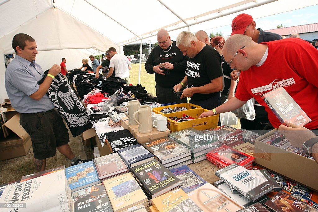 Participants browse through items at a stand at the German far-right Nationaldemokratische Partei Deutschlands - Die Volksunion (National Democratic Party, NPD) 'Pressefest' summer festival, organized by the party's publication, the 'Deutsche Stimme' (the German Voice), on August 11, 2012 in Pasewalk, Germany. The event took place in the German state of Mecklenburg-Vorpommern, known as a stronghold for the NPD, where the party won over 30% of the votes in two districts in state elections in 2011. There have been two attempts to legally ban the right-wing group, in 2003 and 2011, after a neo-Nazi terrorist cell murdered at least nine people of predominently Turkish background as well as one policewoman between 2000 and 2007.