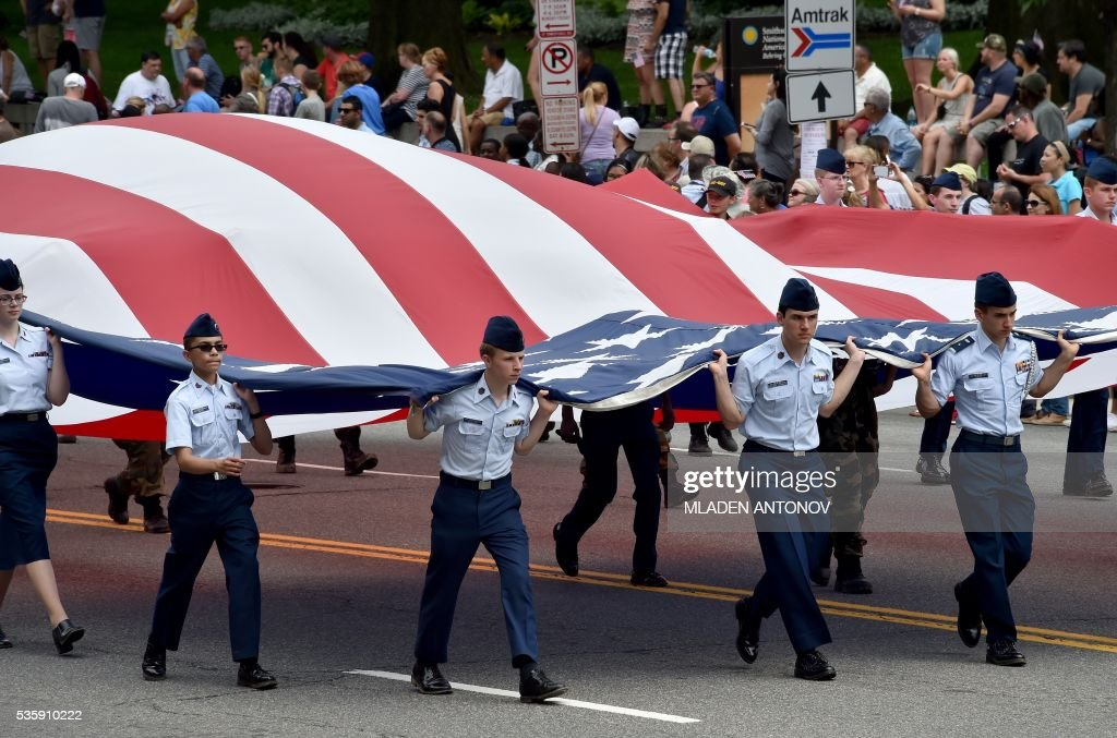 Participants carry a giant US flag during the Memorial Day Parade on Constitution Avenue in Washington DC on May 30, 2016. / AFP / MLADEN