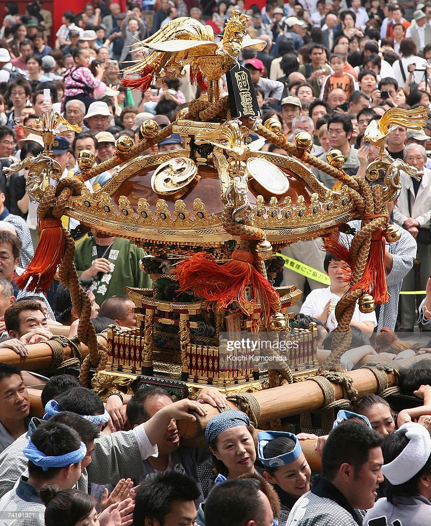 Participants carry a portable shrine during the Sanja Festival at Asakusa Shrine on May 19 2007 in Tokyo Japan About one hundred portable shrines are...