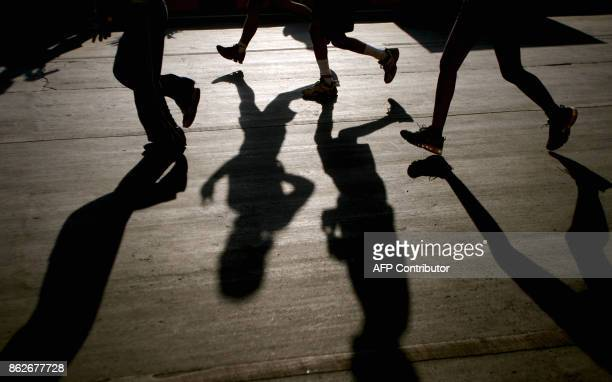 Participants cast shadows on the ground as they take part in the Standard Chartered Mumbai Marathon race in Mumbai 20 January 2008 John Kelai of...