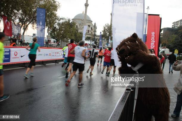 Participants compete as a man in bear suit waves hand during Vodafone 39th Istanbul Marathon at The 15 July Martyrs Bridge in Istanbul Turkey on...