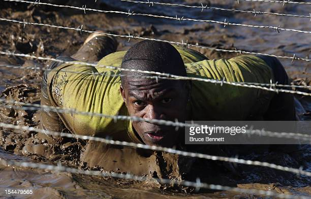 Participants compete in the Tough Mudder event at Raceway Park on October 20 2012 in Englishtown New Jersey