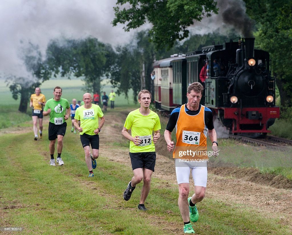 Participants compete with a steam railway in Bruchhausen-Vilsen, northern Germany, on May 29, 2016 during a competition run between the train and the runners. / AFP / dpa / Ingo Wagner / Germany OUT