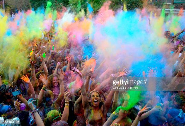 Participants covered in coloured powder gather in central Madrid on August 8 2015 during the second edition of Mossoon Holi Madrid a commercial...