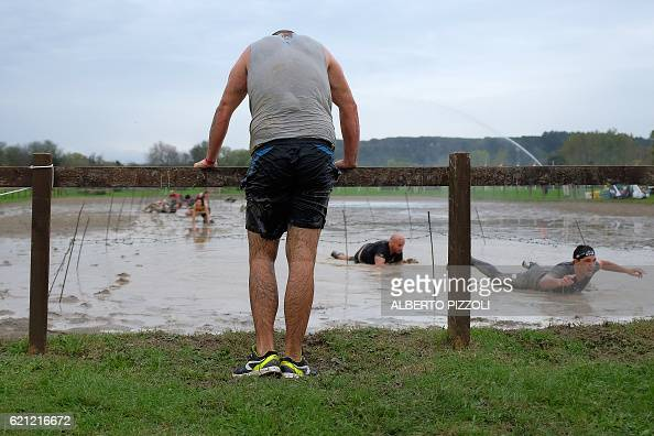 Participants crawl under barbed wire as they take part in the Legion Run a 5kilometer teamoriented run with obstacles of mud fire ice and barbed wire...