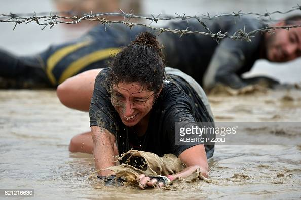 Participants crawl under barbed wire they take part in the Legion Run a 5kilometer teamoriented run with obstacles of mud fire ice and barbed wire in...