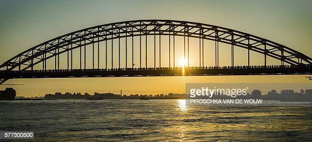 TOPSHOT Participants cross a bridge over the Waal river during the first day of the 100th edition of the annual four days march of Nijmegen on July...