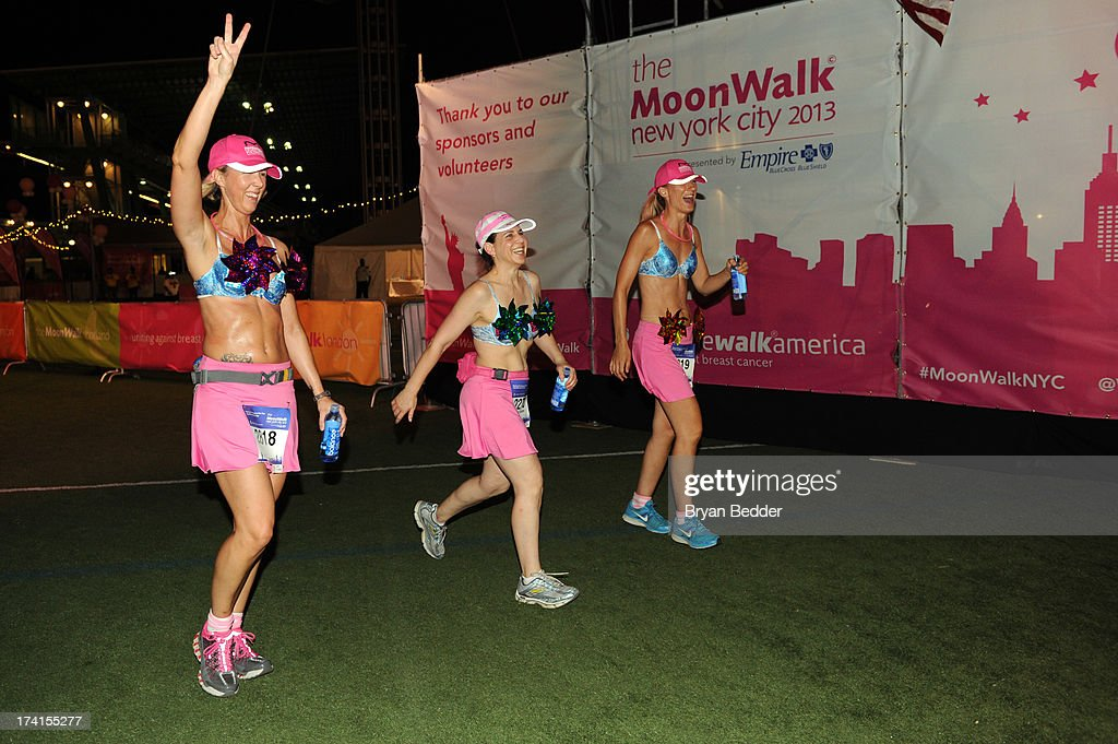 Participants cross the finish line at the first-ever MoonWalk NYC at Randall's Island on July 20, 2013 in New York City.