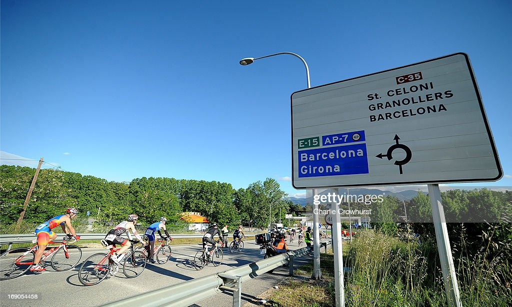 Participants cycle past a road sign for Barcelona during the Challenge Family Triathlon Barcelona on May 19, 2013 in Barcelona, Spain.