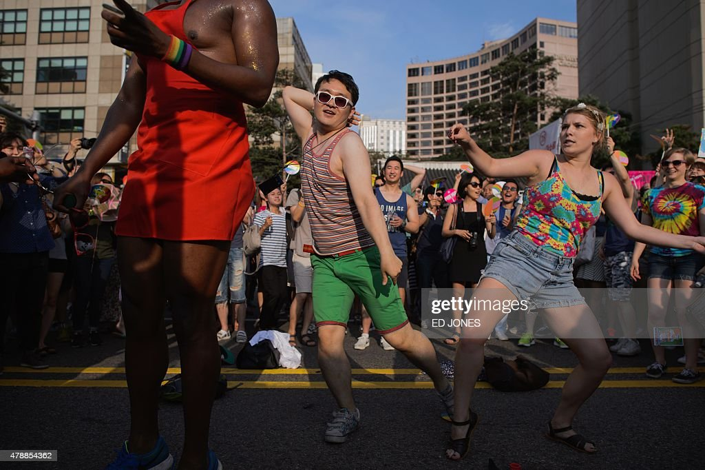 Participants dance during a gay pride parade as part of the 'Korea Queer Festival' in Seoul on June 28, 2015. Thousands of participants of South Korea's annual gay pride parade marched across central Seoul, with many celebrating the US Supreme Court's historic decision allowing same-sex couples to wed. Gay and transgender Koreans live largely under the radar in a country that remains deeply conservative about matters of sexual identity and where many still regard homosexuality as a foreign phenomenon. Thousands of Christian activists stood behind police barriers to wave banners and chant slogans at those taking part, condemning what they called an attempt to turn the South Korean capital into 'Sodom and Gomorrah.' AFP PHOTO / Ed Jones